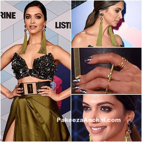 Deepika Padukone donned a cutom-made high slit gown by Monisha Jaising during MTV EMAs event. She just looked stunning in this awesome outfit. Thigh high slit gown just like a wrapped skirt held with a wide black belt along with a black metallic brassiere and shimmered cape with a fashion in trend.   She wore tasseled Valliyan earrings in matching color and black high heels to complete her look.